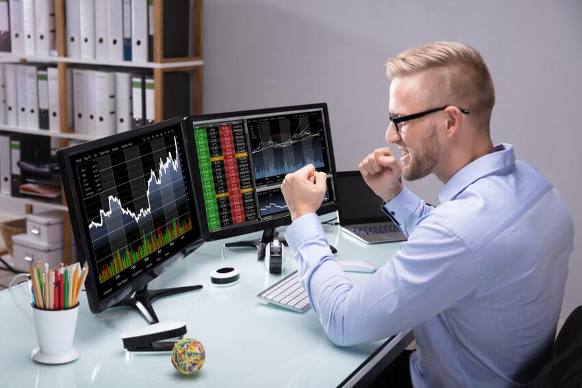 Aktien-Händler vor zwei Computerbildschirmen